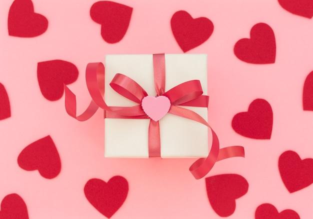 赤いリボンとピンクのハートの白いギフトボックス。バレンタインデーのコンセプト。バレンタイングリーティングカード。フラットレイスタイル。