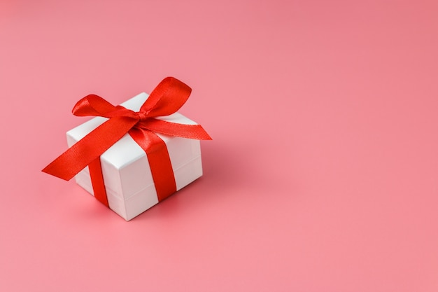White gift box with red strap on colour , engagement ring box