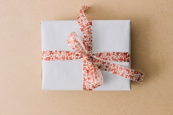 White gift box with ribbon on brown table