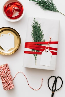 White gift box with tied cypress branch on light table