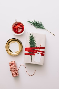 White gift box with tied cypress branch on table