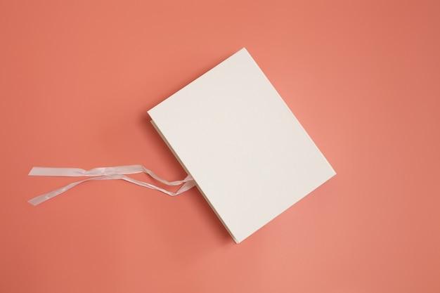 Белая подарочная коробка с развязанным шелковым бантом на розовом фоне