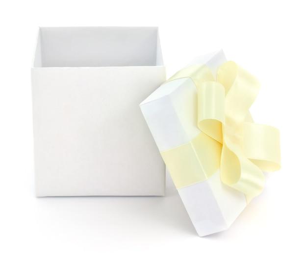 Белая подарочная коробка с желтым бантом на белом фоне