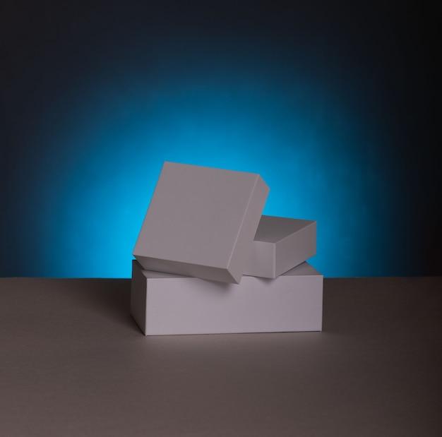 白いギフトボックス。影付きの青い背景に空白のギフトボックスとギフトバッグ。空白のモックアップファイル