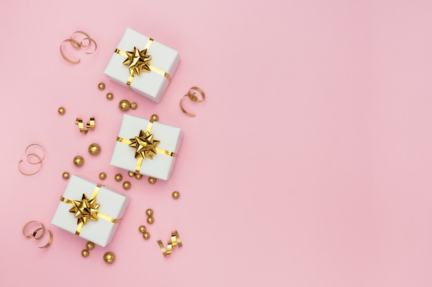 White gift boxes, golden decorations and ornaments on pastel pink background.