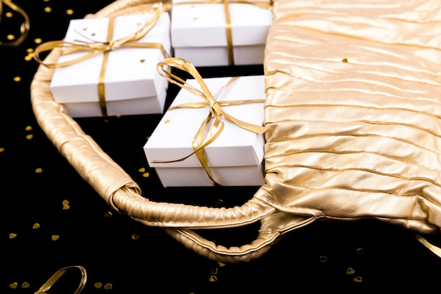 White gift boxes with gold ribbon pop out from golden bag on shine . close up.