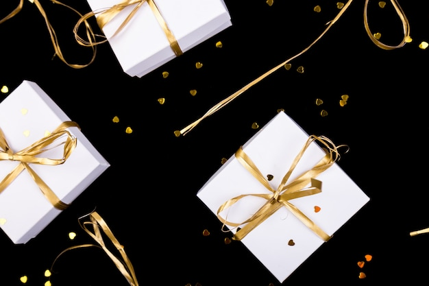 White gift boxes with gold ribbon on shine . flat lay