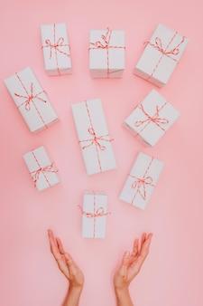 Белые подарочные коробки с красной лентой на розовом фоне, фон на день святого валентина, день рождения, годовщину.