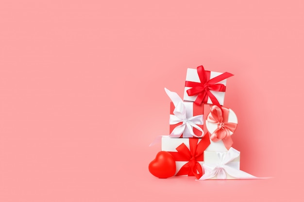 White gift boxes with red satin ribbons on a pink background. festive presents for st. valentine's day, international women's day, wedding or engagement.