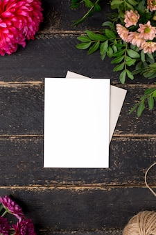 White gift card with beautiful flowers on a dark vintage table