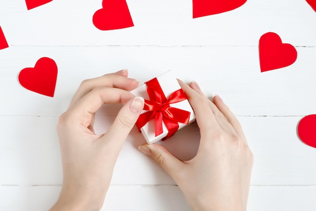 White gift with red ribbon in female hands with hearts around on a white wood