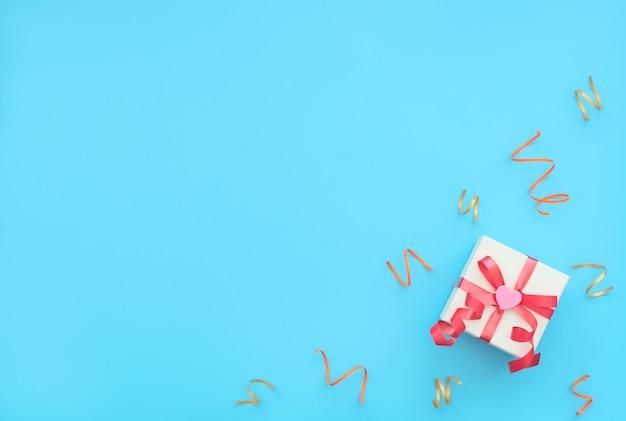 Белая подарочная коробка с красной лентой и розовым сердцем на синем фоне с яркими праздничными лентами.