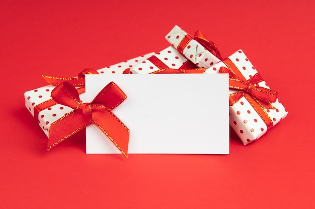 White gifts packed in wrapping paper pot with festive ribbon on red background with note mock up.