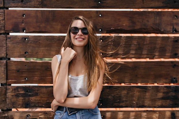 White girl expressing good emotions on wooden wall. portrait of magnificent pale young woman wears dark sunglasses.