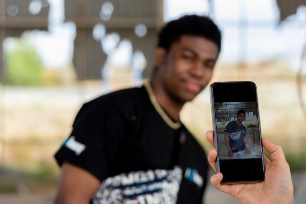 백인 여자는 그녀의 휴대 전화와 함께 흑인 남자의 사진을 복용.