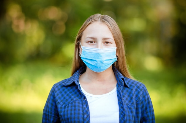 A white girl with dark hair in a blue checked shirt and white t-shirt stands on the street in the summer in a protective medical mask. concept of protection against viral infection and urban smog.