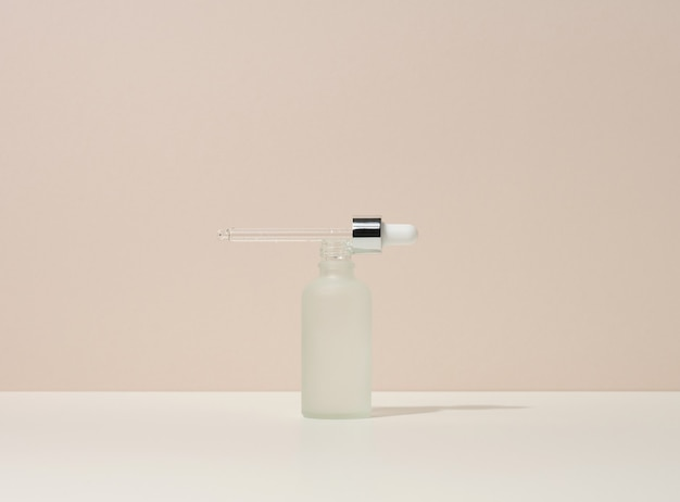 White glass bottle with pipette stands on a beige background. cosmetics spa branding. packaging for gel, serum, advertising and product promotion, mock up