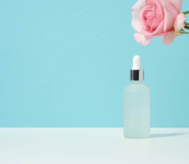 White glass bottle with pipette stands on a blue background. cosmetics spa branding. packaging for gel, serum, advertising and product promotion, mock up