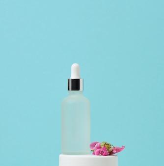 피펫이 있는 흰색 유리병은 파란색 배경에 서 있습니다. 화장품 spa 브랜딩. 젤, 세럼, 광고 및 제품 판촉용 포장, 모형