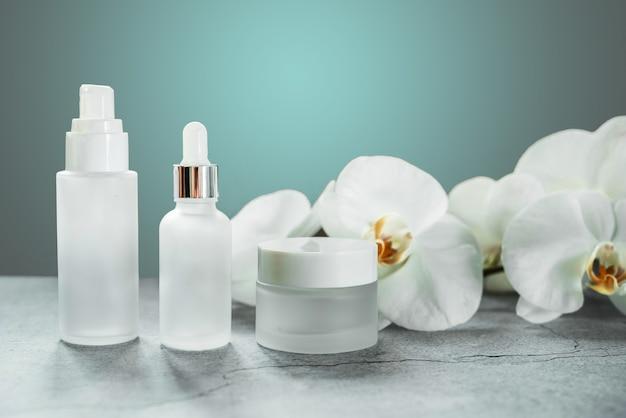 난초 꽃이 배경에 있는 욕실의 흰색 유리 세럼 병과 크림 항아리, 브랜드가 없는 화장품, 스파 화장품 브랜드 흉내