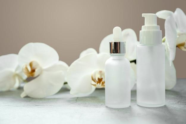 난초 꽃이 배경에 있는 욕실에 디스펜서 모형이 있는 흰색 유리 세럼 병 및 로션 펌프 병, 브랜드가 없는 화장품, 스파 화장품 브랜드 모형