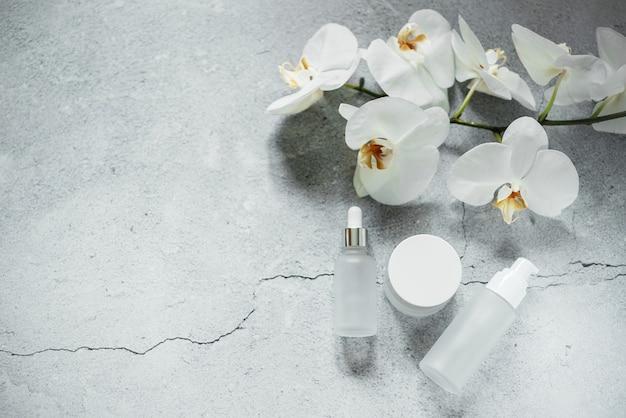 흰색 유리 세럼 병, 로션 펌프 병 및 크림 병 모형은 배경에 난초 꽃이 있는 욕실, 브랜드가 없는 화장품, 스파 화장품 브랜드 모형