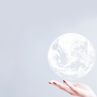 White globe over woman hand gray background