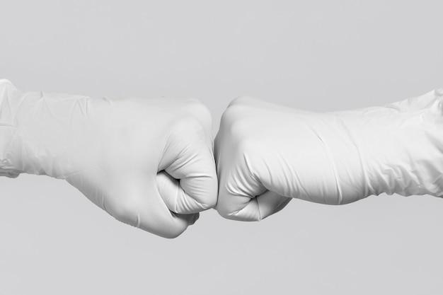 모형용 흰색 장갑. 코로나바이러스와의 전쟁. 주먹 범프 제스처를 만드는 두 의료 노동자.