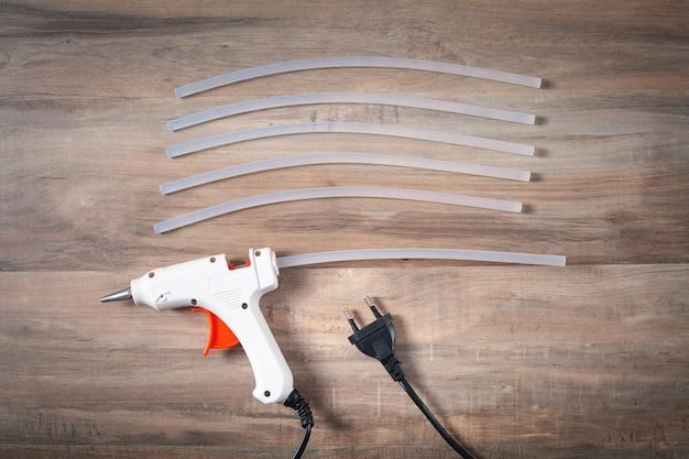 White glue gun with plastic sticks on the wooden background.