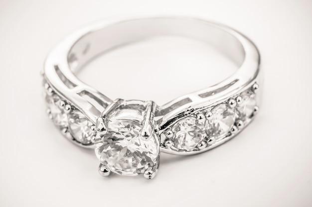 White gold diamond ring on white cream background