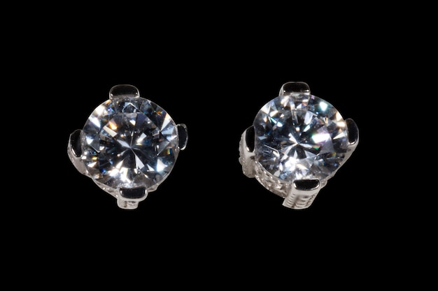 White gold earrings with one larger zircon isolated on a black background