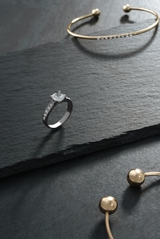 White gold ring with diamond and gold bracelets on dark stone background