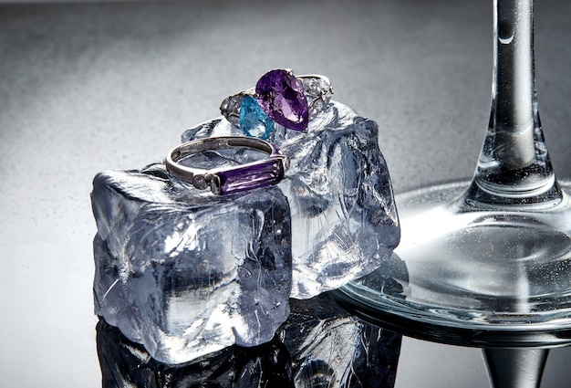 White gold rings with amethyst and blue topaz on ice cubes on a gray background with reflection.