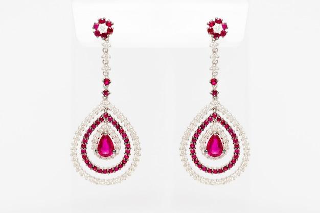 ダイヤモンドと明るい背景に赤い貴重な宝石と白い黄金のイヤリング。長い黄金のイヤリング。ファッション高級アクセサリー。