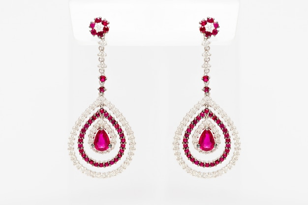 White golden earrings with diamonds and red precious gems on light background. long golden earrings. fashion luxury accessories.