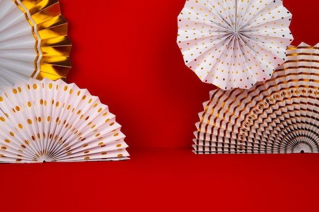 White and golden paper fans on red background.