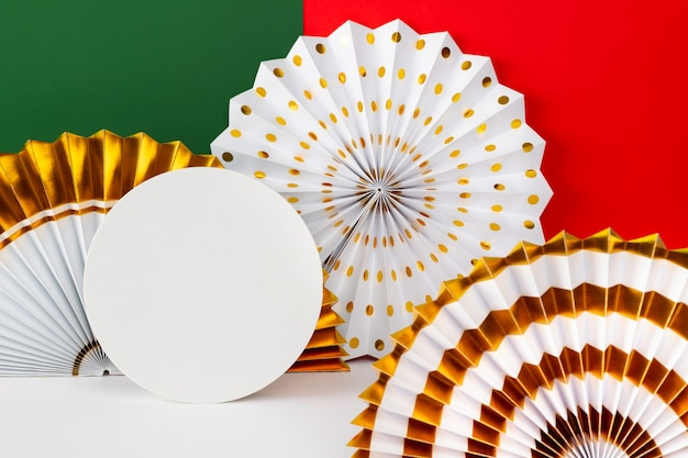 White and golden paper fans on red and green background.