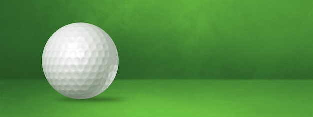 White golf ball isolated on a green studio banner.