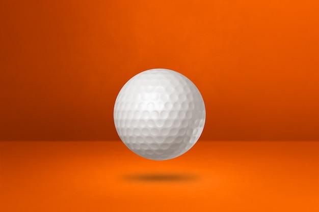 オレンジ色のスタジオの背景に分離された白いゴルフボール。 3dイラスト
