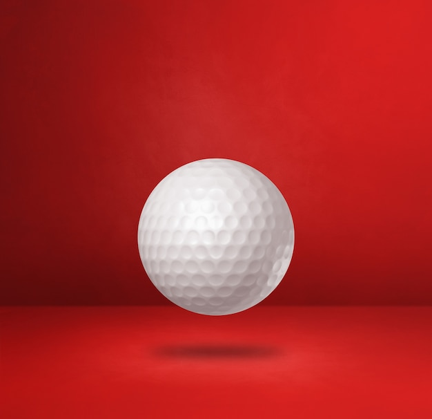 White golf ball isolated on a red studio background. 3d illustration