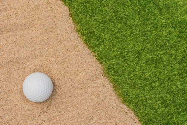 White golf ball in sand bunker on golf court