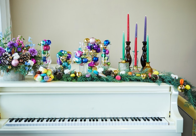 White grand piano decorated in new year's style, christmas tree, christmas toys and balls, candles and macarons