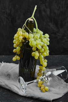 White grapes around a bottle of wine and an empty glass on dark surface with grey tablecloth