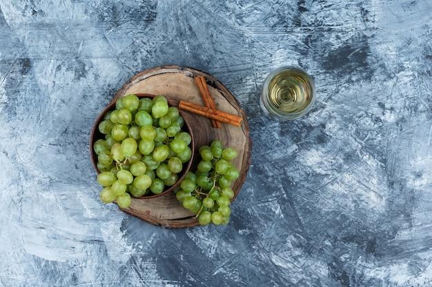 Uva bianca, cannella su una tavola di legno con un bicchiere di whisky vista dall'alto su uno sfondo di marmo blu scuro