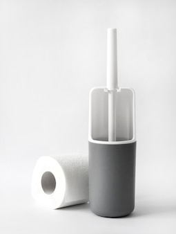 White and gray plastic toilet brush and roll of toilet paper on white background
