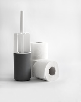 White and gray plastic toilet brush and toilet paper on white surface