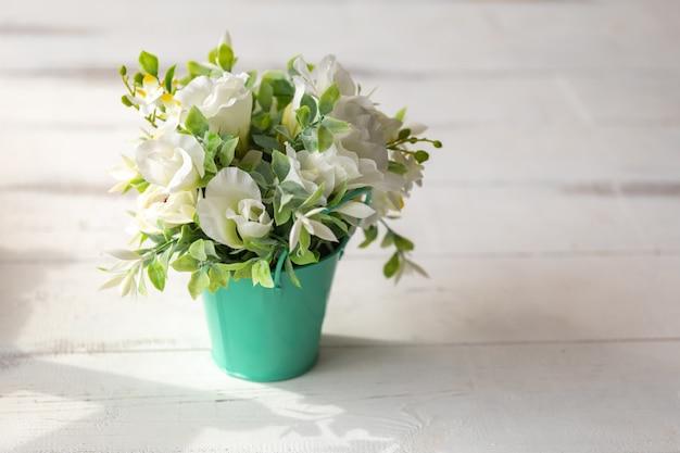 흰색 나무 테이블에 녹색 금속 양동이에 흰색 녹색 인공 꽃. 공간을 복사하십시오.