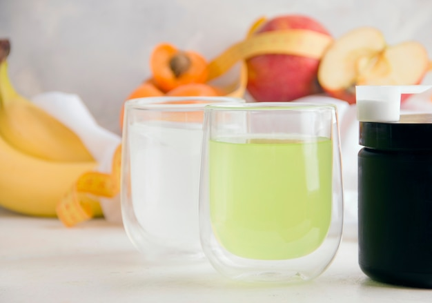 White and green fitness drinks on light background