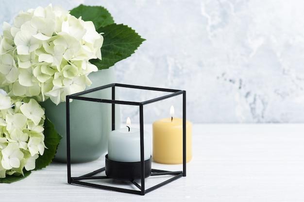 ポットと火のともったろうそくの白緑色のオルテンシアの花
