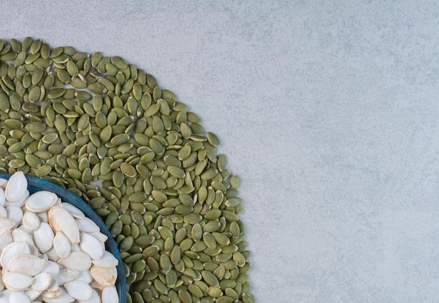 Semi di zucca bianchi e verdi su fondo concreto.